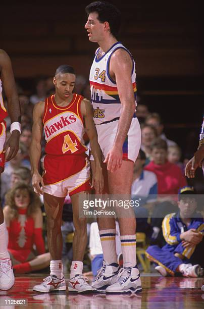 Spud Webb of the Atlanta Hawks tries to maneuver around a much larger opponent during a NBA game at McNichols Sports Arena in Denver Colorado in 1989