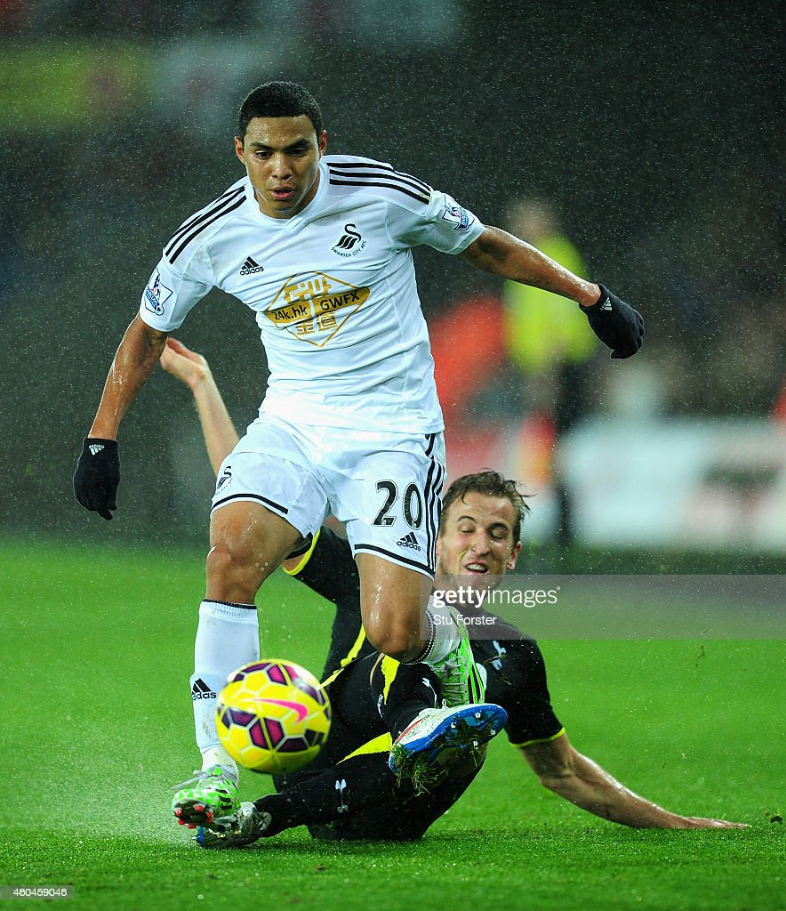 Spurs player Harry Kane challenges Swansea player Jefferson Montero during the Barclays Premier League match between Swansea City and Tottenham Hotspur at Liberty Stadium on December 14, 2014 in Swansea, Wales.