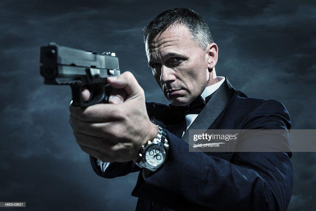 Spy in Tuxedo Aiming Gun : Stock Photo