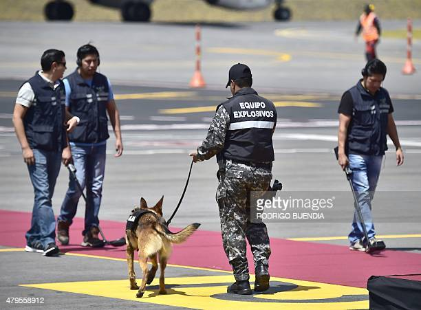 A squad bomb member with a sniffer dog check the stage hours before the arrival of Pope Francis at the Mariscal Sucre international airport in Quito...