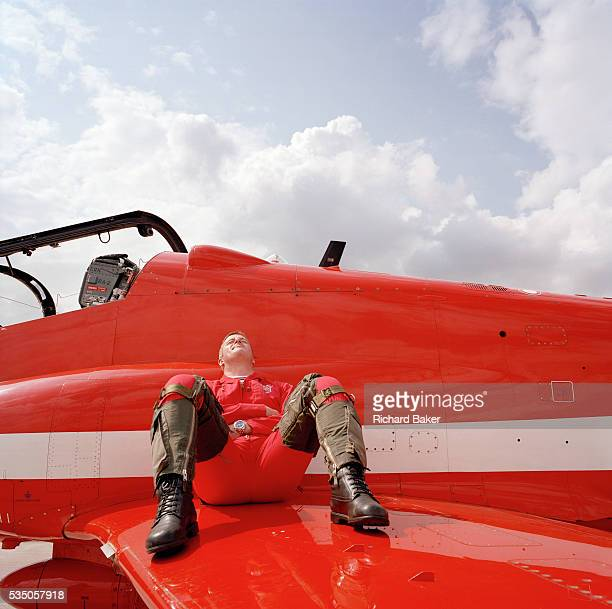 Squadron Leader David Thomas of the elite 'Red Arrows' Britain's prestigious Royal Air Force aerobatic team sits on the wing of his Hawk jet aircraft...