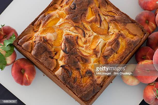 A square baked peach cake on a board with fresh peaches. Fruits. Organic fresh food on a farmstand.