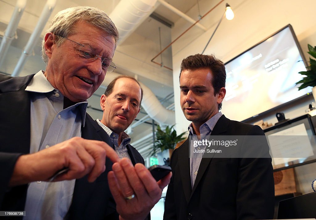 Square CEO Jack Dorsey (R) and House Ways and Means Committee Chairman Dave Camp (C) (R-MI) look on as Senate Finance Committee Chairman Max Baucus (L) (D-MT) attempts to download the Square Wallet app while touring the Square headquarters on August 19, 2013 in San Francisco, California. Senators Max Baucus (D-MT) and Dave Camp (R-MI) continued their Tax Reform Tour with a visit to the headquarters of mobile payment company Square. The tour is taking the two senators across the nation to speak to American people about how to fix the nation's broken tax code to benefit families and job creators.