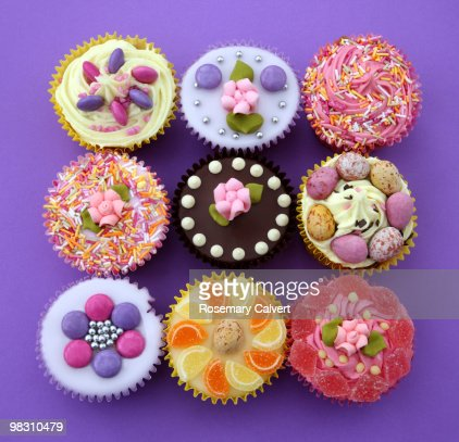 Square of colourful cupcakes, purple background : Stock Photo