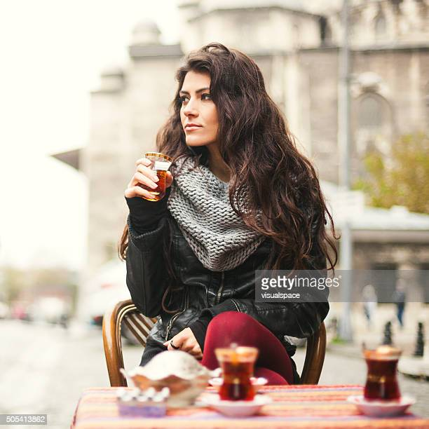 Square Portrait of a Young Turkish Woman Enjoying Tea Outdoors