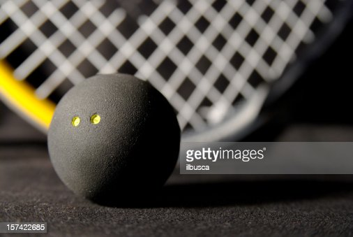 Squash ball and racket on black