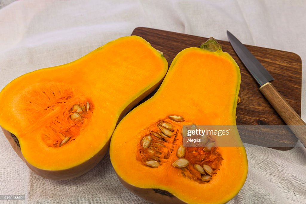 Squash cut in half on a wooden board : Stock Photo