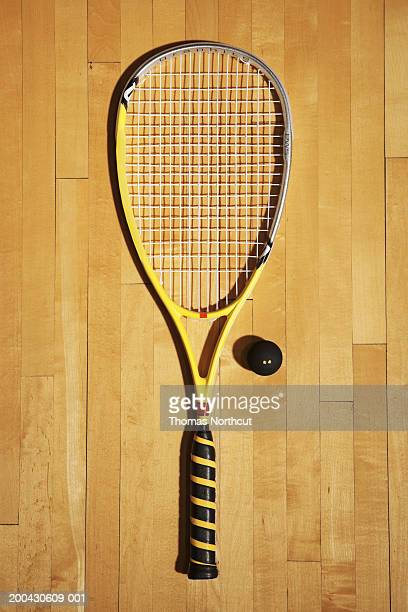 Squash racket and ball on hardwood floor of squash court