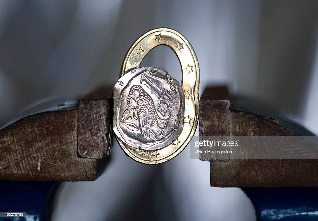 Squashed Greek 1 Euro coin in a vice, on February 12, 2015 in Bonn, Germany.