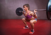 Fit female athlete is performing squats .