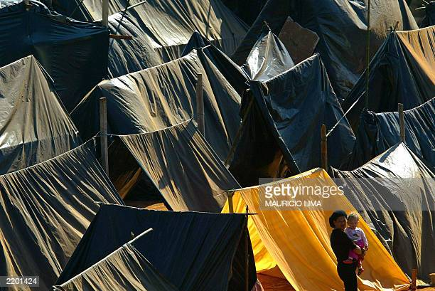 A squatter carries a baby between tents installed on lands of an inactive Volkswagen factory in Sao Bernardo do Campo 25 km from Sao Paulo Brazil on...