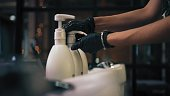 Hairdresser in black gloves is squeezing shampoo on hand in beauty salon.