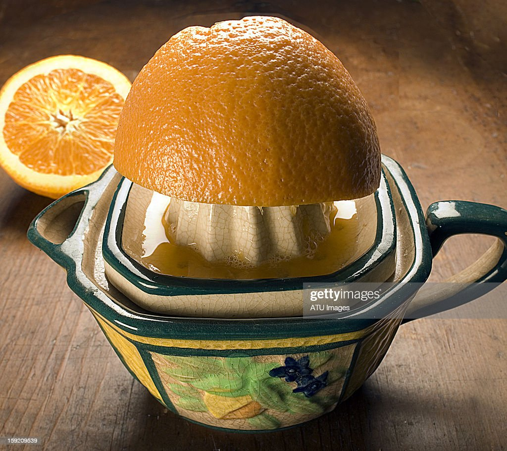 Squeezing an orange on a ceramic squeezer : Stock Photo