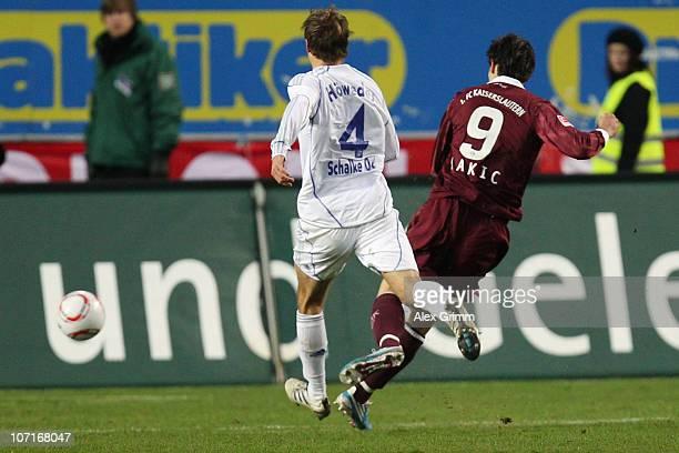 Srdjan Lakic of Kaiserslautern scores his team's third goal against Benedikt Hoewedes of Schalke during the Bundesliga match between 1 FC...