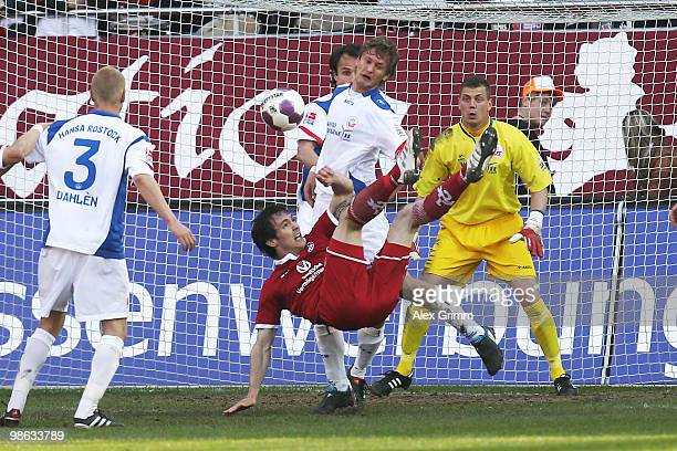 Srdjan Lakic of Kaiserslautern tries to score with a bicycle kick against Kai Buelow and goalkeeper Alexander Walke of Rostock during the Second...