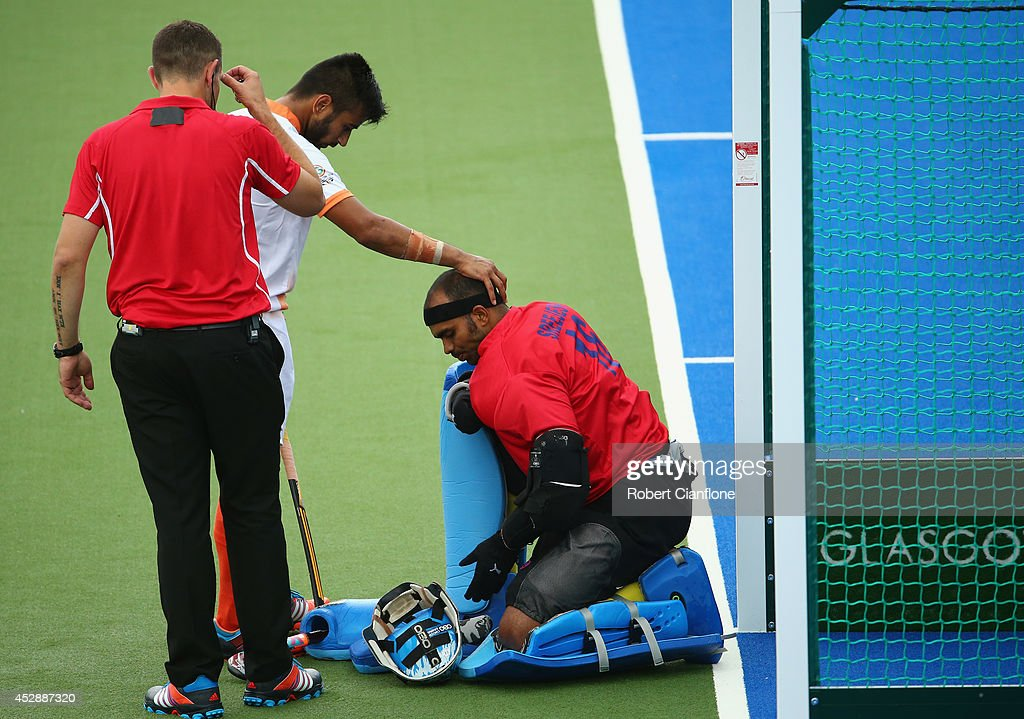 Sreejesh Parattu Raveendran of India is checked by a team mate after he was struck in the face during the men's preliminaries match between India and Australia at the Glasgow National Hockey Centre during day six of the Glasgow 2014 Commonwealth Games on July 29, 2014 in Glasgow, United Kingdom.