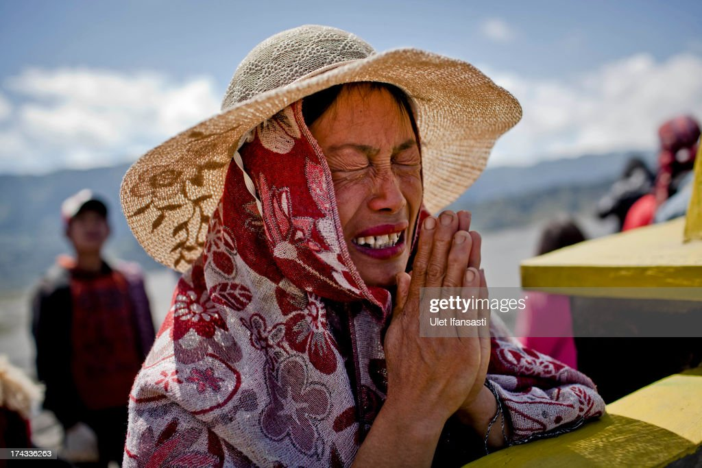 Sri Harminah (40), a Tenggerese worshipper cries as prays to ancestors during the Yadnya Kasada Festival at the crater of Mount Bromo on July 23, 2013 in Probolinggo, Indonesia. The festival is the main festival of the Tenggerese people and lasts about a month. On the fourteenth day, the Tenggerese make the journey to Mount Bromo to make offerings of rice, fruits, vegetables, flowers and livestock to the mountain gods by throwing them into the volcano's caldera. The origin of the festival lies in the 15th century when a princess named Roro Anteng started the principality of Tengger with her husband Joko Seger, and the childless couple asked the mountain Gods for help in bearing children. The legend says the Gods granted them 24 children but on the provision that the 25th must be tossed into the volcano in sacrifice. The 25th child, Kesuma, was finally sacrificed in this way after initial refusal, and the tradition of throwing sacrifices into the caldera to appease the mountain Gods continues today.