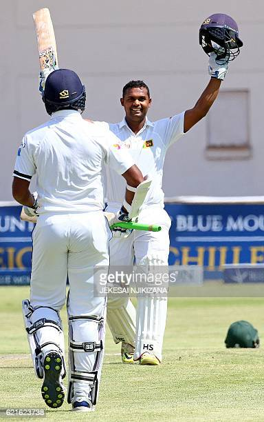 Sri Lanka batsman Asela Gunaratne raises his bat after reaching 100 runs during the second day of the second cricket Test match between Sri Lanka and...