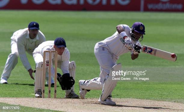 Sri Lanka batsman Hashan Tillakaratne drives a delivery from Glamorgan's Robert Croft as wicketkeeper Mark Wallace looks on during the first days...