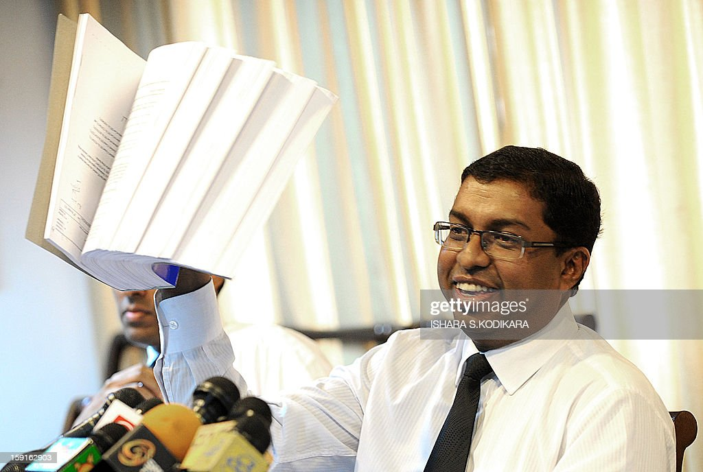 Sri Lanka Chief Justice Shirani Bandaranayake's lawyer Saliya Peiris holds up the documents given to him by a panel of ruling party MPs to support allegations of financial and professional misconduct of the top judge, during a press conference in Colombo on January 9, 2013. Peiris says he was given less than 24 hours to study the documents and prepare a defence, but Bandaranayake decided to walk out of the hearing last month saying it was unfair. She faces removal by parliament following a vote in parliament on January 11, 2013. AFP POHOTO/ Ishara S.KODIKARA