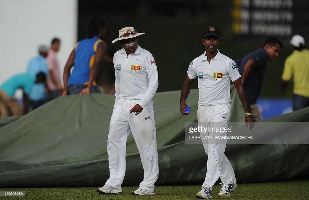 Sri Lanka cricket captain Mahela Jayawardene (L) and teammate Nuwa Kulasekara (R) leave the pitch as rain stopped play during the first day of the second and final Test match between Sri Lanka and New Zealand at the P. Sara Oval Cricket Stadium in Colombo on November 25, 2012.