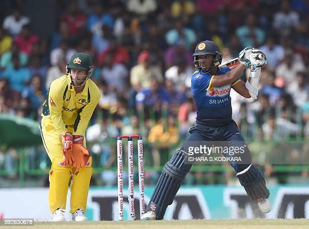 Sri Lanka cricketer Kusal Mendis plays a shot as Australian wicketkeeper Mathew Wade looks on during the first One Day International cricket match...