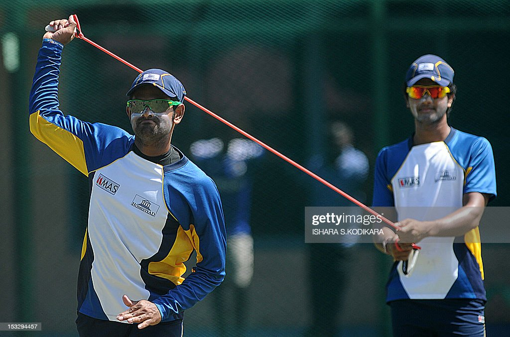 Sri Lanka cricketers Lahiru Thirimanne (L) and Dinesh Chandimal (R) stretch during an ICC Twenty20 Cricket World Cup practice session ahead of their semi-final match against Pakistan in Colombo on October 3, 2012. AFP PHOTO / Ishara S