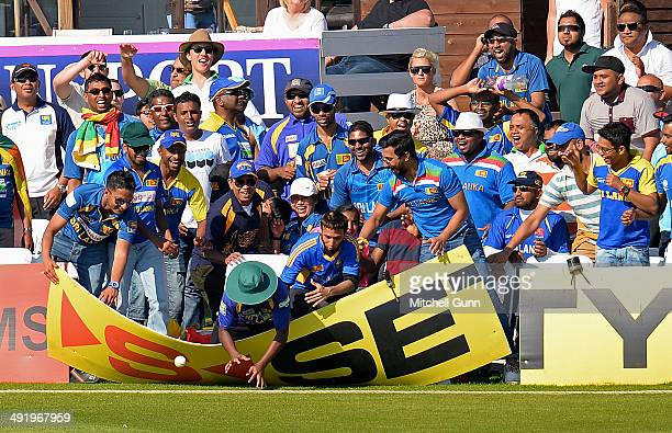 Sri Lanka fans collapse an advertising board while attempting to catch the match ball during the T20 match between The Sussex Sharks and Sri Lanka...