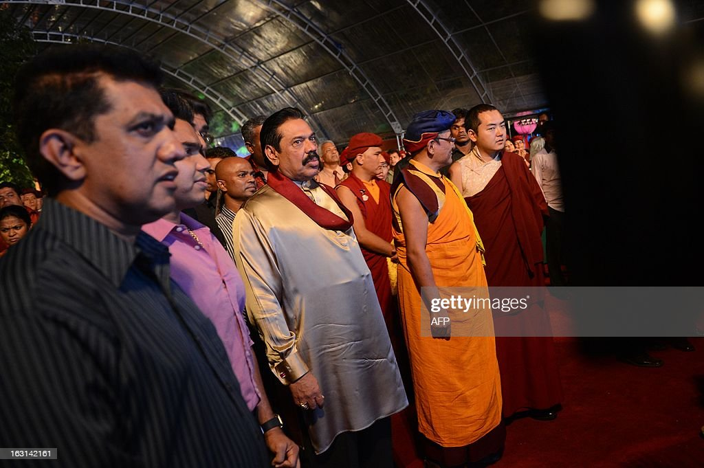 Sri Lanka President Mahinda Rajapakse (C) looks on during the launch of a website for the state-run film studious in the southern district of Hambantota on March 5, 2013. The president has pledged to turn the arid region, his home constituency, into a new commercial and arts capital of the country emerging from nearly four decades of ethnic bloodshed. AFP PHOTO / Ishara S. KODIKARA