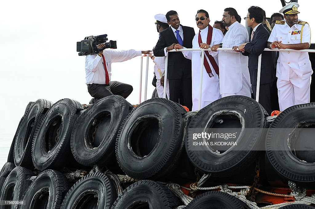 Sri Lanka President Mahinda Rajapakse (C) travels aboard a tug-boat inside the Colombo harbour to ceremonially launch the Chinese-built Colombo International Container Terminal (CICT) in Colombo on August 5, 2013. Sri Lanka launched its biggest port with Chinese funding to turn Colombo into a strategic shipping hub along the world's most lucrative trading route. AFP PHOTO/ Ishara S. KODIKARA