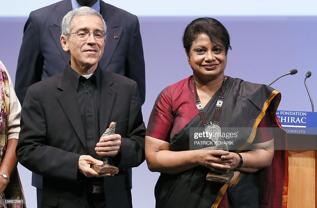 Sri Lanka Radhika Coomaraswamy (R), laureate of the jury's special prize and Father Francisco de Roux, laureate for the prize for conflict prevention, celebrates during the ceremony of release of the Jacques Chirac Foundation's 2012 Award for the prevention of conflicts, on November 22, 2012 at the Quai Branly Museum in Paris. AFP PHOTO PATRICK KOVARIK