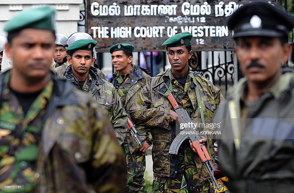 Sri Lanka Special Task Force (STF) soldiers stand guard with other police officials outside the High Court in the capital Colombo on January 10, 2013. Sri Lanka's lawyers staged a strike Thursday to protest the impeachment of the country's top judge which has raised concern about judicial independence on the previously war-ravaged Indian Ocean island. Work in court houses came to a stand still as some 11,000 lawyers of the influential Bar Association stayed away and protested in the centre of the capital Colombo after being prevented from marching to parliament. AFP POHOTO/ Ishara S