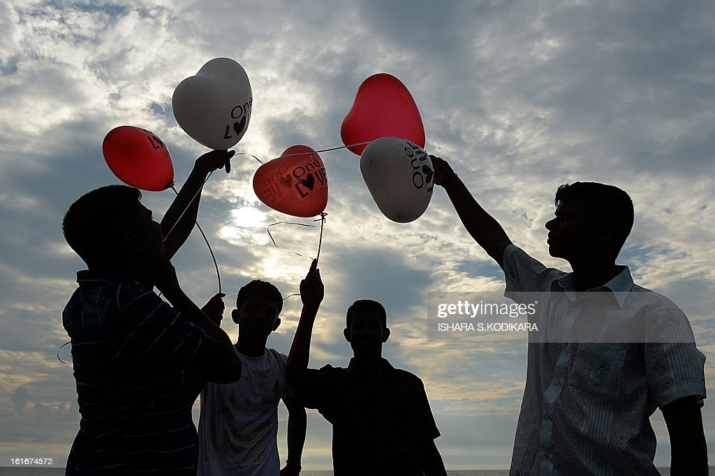 Sri Lankan activists hold up balloons during a celebration of Valentine's Day in Colombo on February 14, 2013. Valentine's Day in mainly Buddhist Sri Lanka is often noted as a marketing opportunity for hotels and gift shops capitalising on the holiday. AFP PHOTO/Ishara S