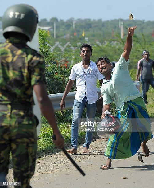 Sri Lankan activists lead by Buddhist monks pelt stones at police during a protest in the southern port city of Hambantota on January 7 2017 Sri...