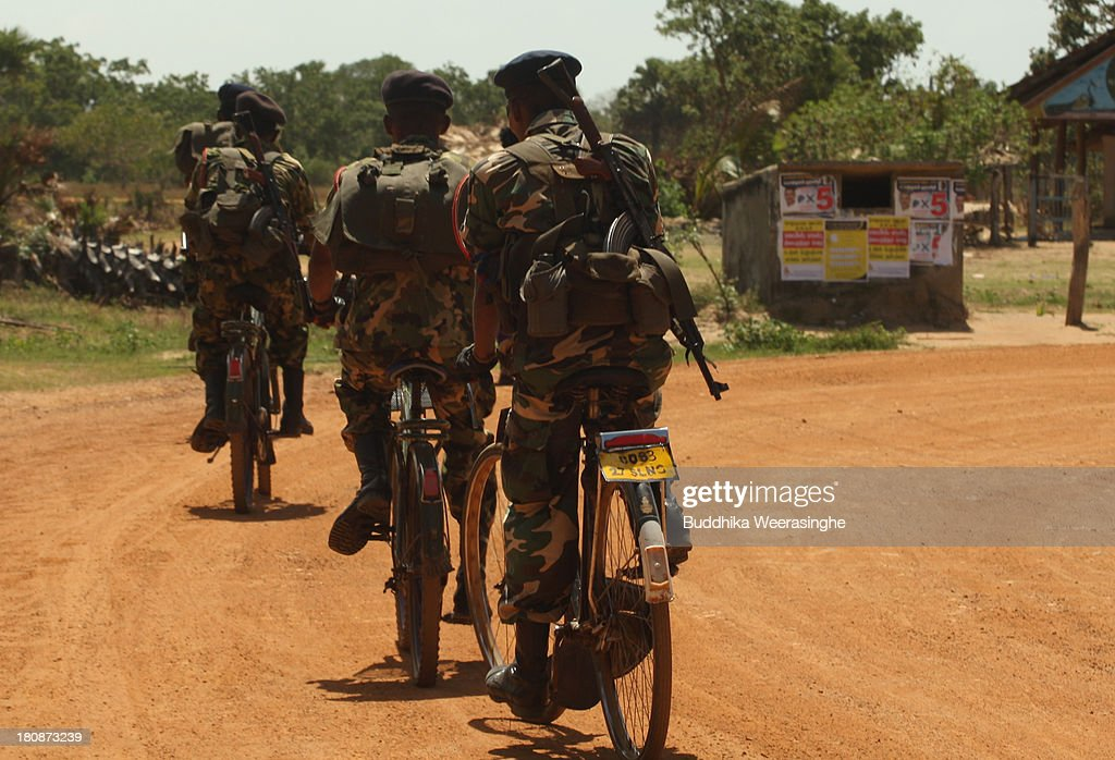 Sri Lankan army soldiers patrol a street beside upcoming election campaign posters on a wall at a former rebel capital on September 17 2013 in...