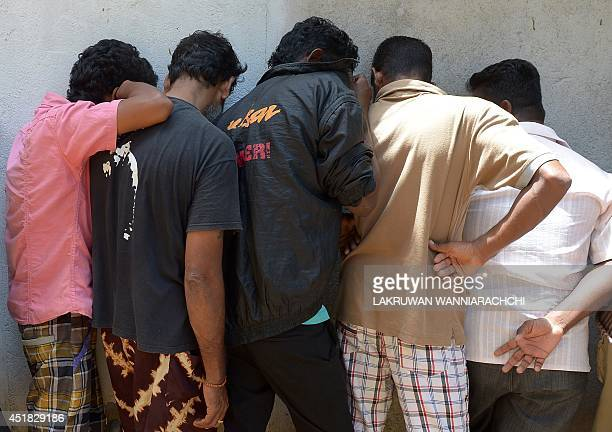Sri Lankan asylum seekers sent back by Australia cover their faces as they wait to enter the magistrate's court in the southern port district of...