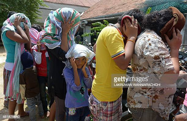 Sri Lankan asylum seekerS sent back by Australia prepare to enter the magistrate's court in the southern port district of Galle on July 8 2014 Sri...