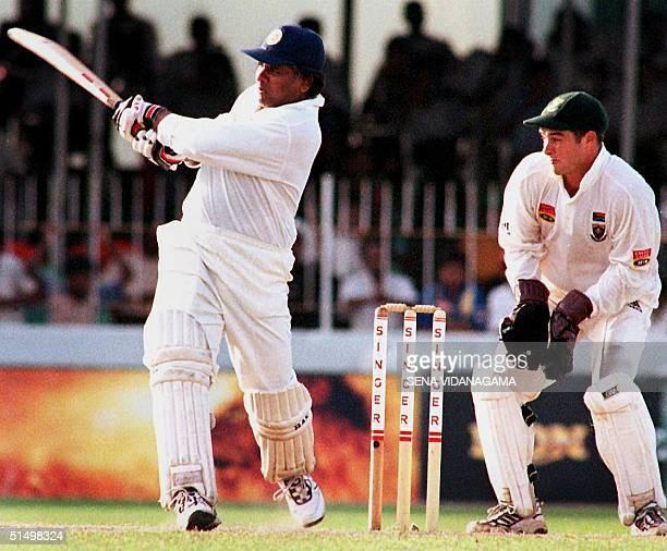 Sri Lankan batsman Arjuna Ranatunga drives the ball as South African wicket keeper Mark Boucher looks on during the final cricket test between Sri...