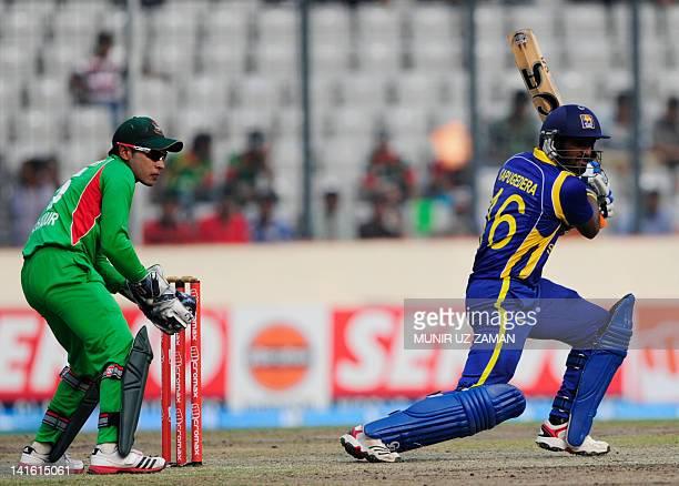 Sri Lankan batsman Chamara Kapugedera plays a shot as captain Mushfiqur Rahim looks on during the one day international Asia Cup cricket match...
