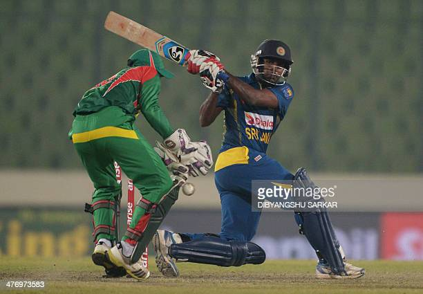 Sri Lankan batsman Chaturanga de Silva plays a shot as Bangladeshi wicketkeeper Anamul Haque looks on during the tenth match of the Asia Cup oneday...