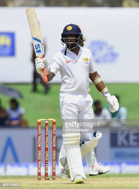 Sri Lankan batsman Dilruwan Perera raises his bat to the crowd after scoring a halfcentury during the third day of the first Test match between Sri...