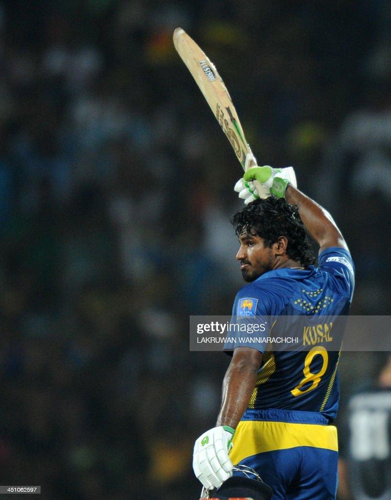 Sri Lankan batsman Kusal Perera raises his bat to the crowd after scoring a half-century (50 runs) during the second Twenty20 cricket match between Sri Lanka and New Zealand at the Pallekele International Cricket Stadium in Pallekele on November 21, 2013.