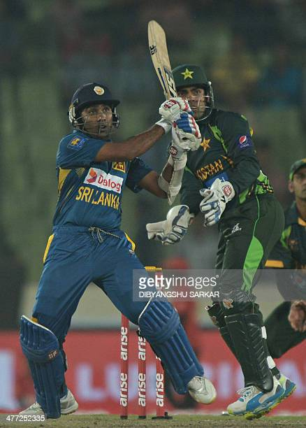 Sri Lankan batsman Mahela Jayawardene plays a shot as Pakistani wicketkeeper Umar Akmal looks on during the final match of the Asia Cup oneday...