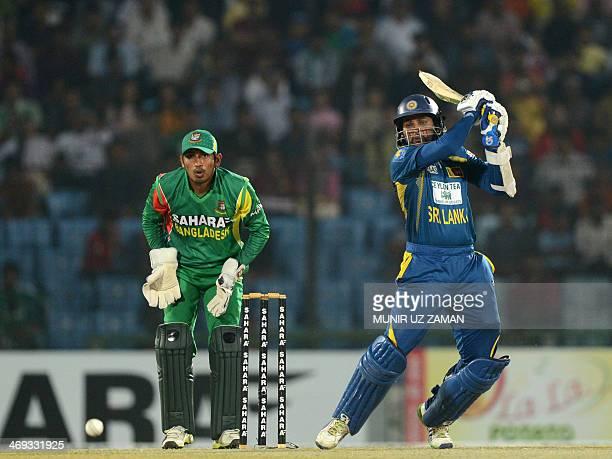 Sri Lankan batsman Tillakaratne Dilshan plays a shot as Bangladeshi wicket keeper Anamul Haque looks on during the second T20 cricket match between...