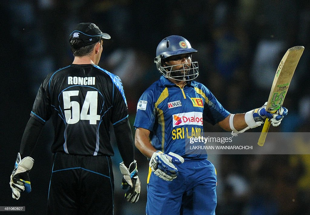Sri Lankan batsman Tillakaratne Dilshan (R) raises his bat to the crowd after scoring a half-century (50 runs) during the second Twenty20 cricket match between Sri Lanka and New Zealand at the Pallekele International Cricket Stadium in Pallekele on November 21, 2013.