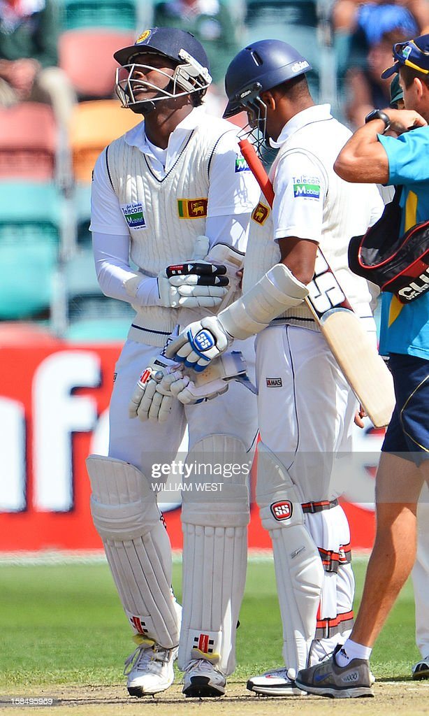 Sri Lankan batsmen Angelo Mathews (L) is in pain after been hit by a delivery from Australian paceman Mitchell Starc as teammate Thilan Samaraweera (R) looks on on the final day of the first cricket Test match, in Hobart on December 18, 2012. AFP PHOTO/William WEST IMAGE