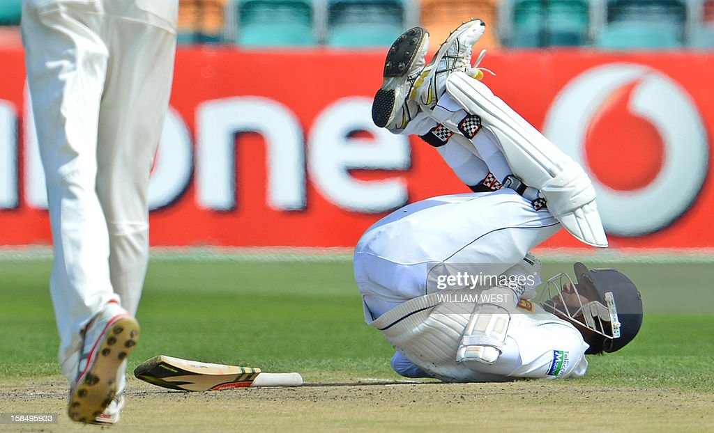 Sri Lankan batsmen Angelo Mathews (R) rolls on the ground in pain after been hit by a delivery from Australian paceman Mitchell Starc (L) on the final day of the first cricket Test match, in Hobart on December 18, 2012. AFP PHOTO/William WEST IMAGE RESTRICTED TO EDITORIAL USE - STRICTLY NO COMMERCIAL USE