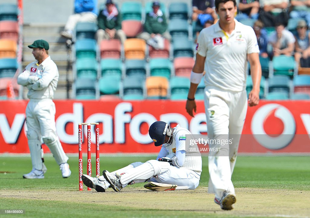 Sri Lankan batsmen Angelo Mathews (C) sits on the ground in pain after been hit by a delivery from Australian paceman Mitchell Starc (R) as wicketkeeper Matthew Wade (L) looks away on the final day of the first cricket Test match, in Hobart on December 18, 2012. AFP PHOTO/William WEST IMAGE RESTRICTED TO EDITORIAL USE - STRICTLY NO COMMERCIAL USE
