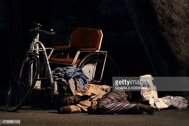 A Sri Lankan beggar sleeps on the road in Colombo on March 6 2014 Sri Lanka's economy recorded 80 percentplus growth for two straight years after...
