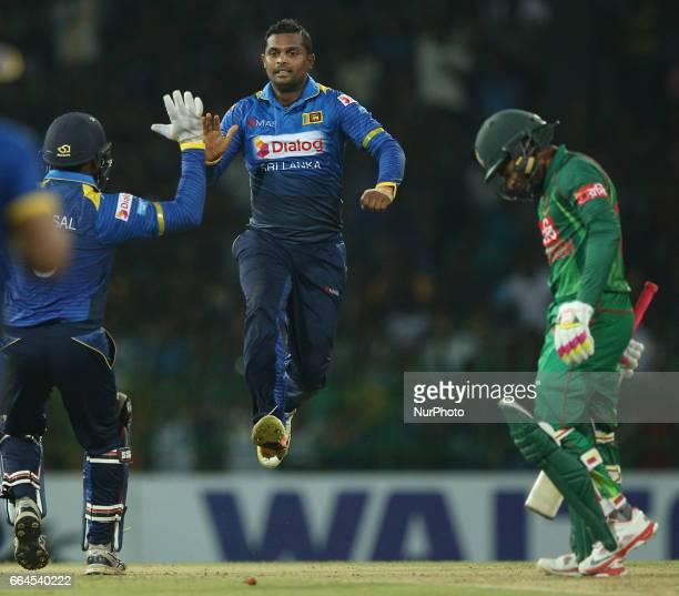 Sri Lankan bowler Asela Gunaratne center celebrates with Kusal Perera the dismissal of Bangladeshi batsman Mushfiqur Rahim in green during the first...